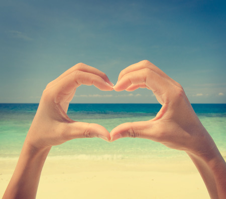 blue sky thinking: hands with love sign on beach, vintage retro filter  Stock Photo