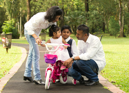 outdoor activities: indian family teaching their kids cycling in the outdoor park