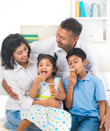 Familia india que goza comiendo helado indoor Foto de archivo - 26886750