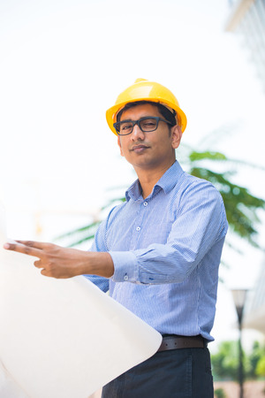 indian male architect holding plans with construction background   photo