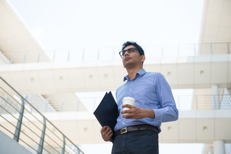 indian business male with coffee and folder photo