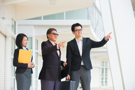 assessing: asian business team pointing somewhere in office background   Stock Photo