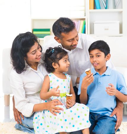 feliz familia india que goza comiendo helado indoor Foto de archivo