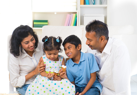 happy indian family enjoying eating ice cream indoor photo