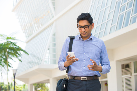 indian male: indian male business man reading or using smart phone Stock Photo