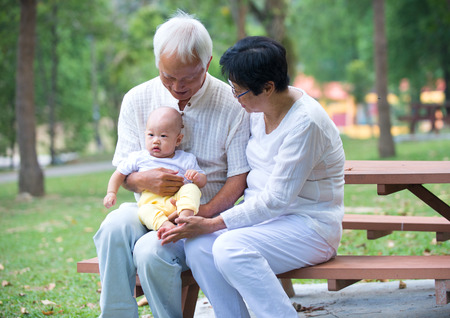 chinese grandfather playing with baby grandson at outdoor photo