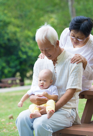asian grandparents playing with baby grandson at outdoor photo