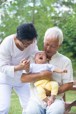 asian baby crying while being comforted by grandparents   photo