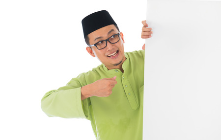 aidilfitri: malay male with blank card during hari raya Eid al-Fitr aidilfitri celebration