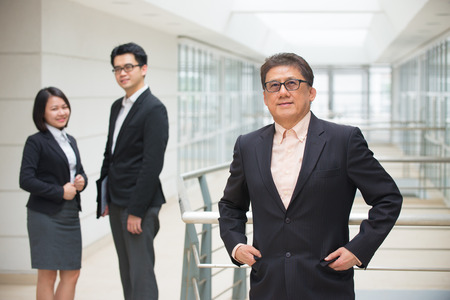 asian business team: senior asian business ceo with team on background