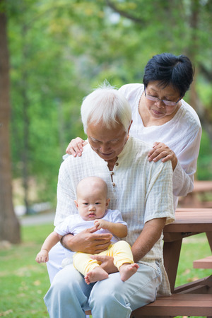 asian family outdoor: asian grandparents playing with baby grandson at outdoor