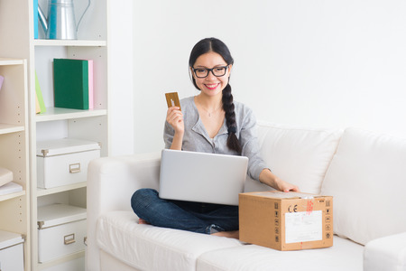 smiling asian girl online shopping on sofa  photo