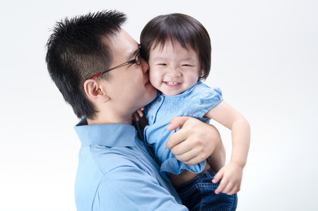 asian father and daughter on plain background