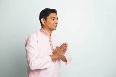 young indian male with Pranamasana greetings sign on traditional dress with plain background
