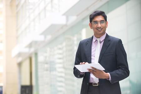 confianza: ejecutivo de negocios indio que trabaja en la computadora de la tableta en la oficina con copyspace en izquierda