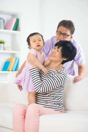 asian grand parents with crying grand daugther  photo