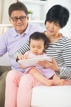 grand sons: asian grand parents teaching grand son with tablet