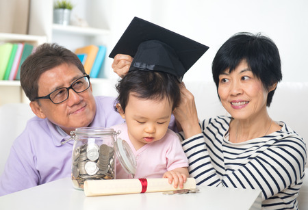 asian grand parents with grand daugther education saving concepts Imagens