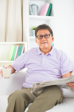 senior asian chinese reading newspaper and drinking milk on a sofa in home photo