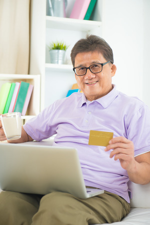 senior asian male online shopping from home photo