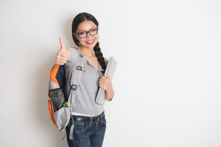 chinese adult:  young chinese female student with thumbs up and plain background