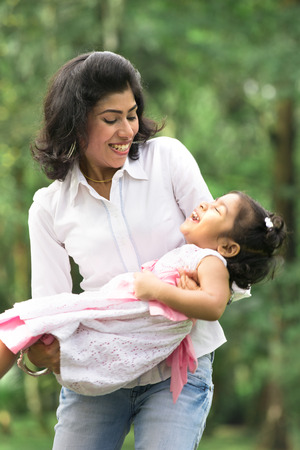 indian mother carrying daughter playing in outdoor park photo