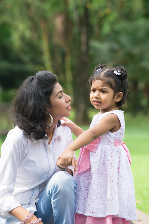 parent and child: indian mother conforting her daughter in outdoor park Stock Photo