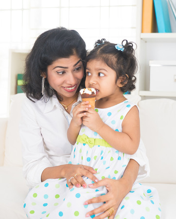 indian mother enjoying ice cream with her daughter on lifestyle background photo