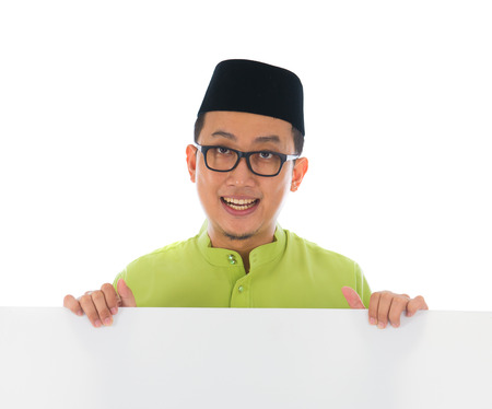malay male with blank card during hari raya Eid al-Fitr aidilfitri celebration   photo