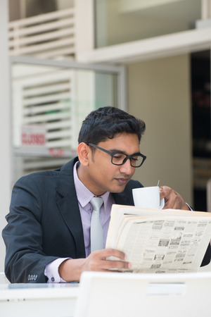 indian business male with newspaper and coffee at a cafe photo
