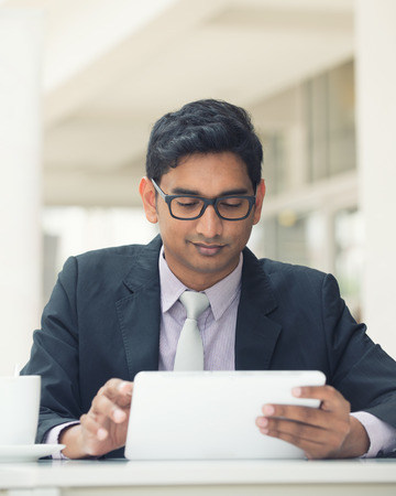 young indian business man with a tablet computer and coffee at a cafe photo