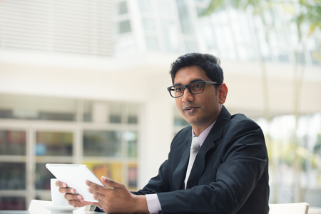 young indian business man with a tablet computer and coffee at a cafe Stock Photo