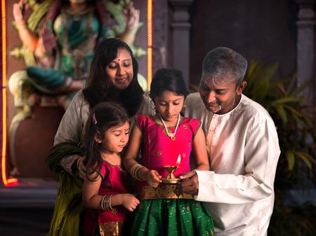 an oil lamp: indio que celebra la familia de Diwali, fesitval de luces en el interior de un templo Foto de archivo