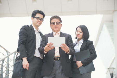 singaporean: singaporean business team meeting over office background