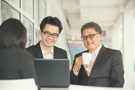 Korean business people gathered together at a table discussing an interesting idea restaurant photo
