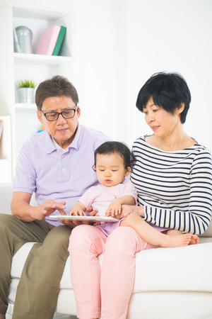 asian grand parents teaching grand son internet with a tablet photo