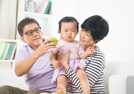 asian grand parents comforting their spoilt crying grand daugther   photo