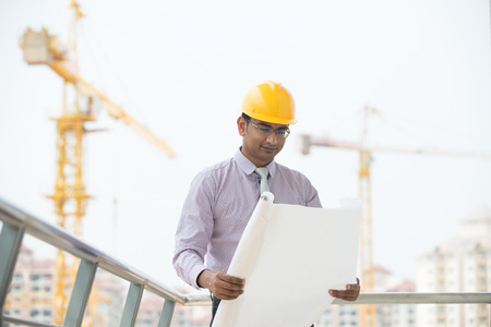 indian male engineer reading plans with construction background photo