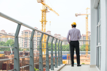 indian male engineer inspecting site with construction background photo