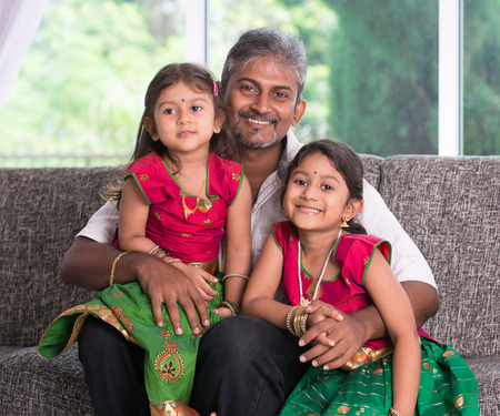single family house: indian father with his daughter smiling and lookin at camera on living room