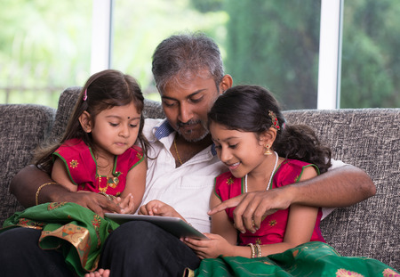 asian indian: indian father with his daughter using a tablet computer on living room