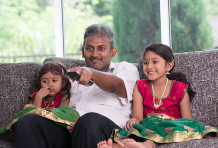 indian father watching tv with his daughter on living room Stock Photo