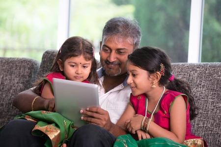 indian father with his daughter using a tablet computer on living room
