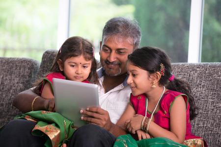 fille indienne: père indien avec sa fille en utilisant un ordinateur tablette sur le salon Banque d'images