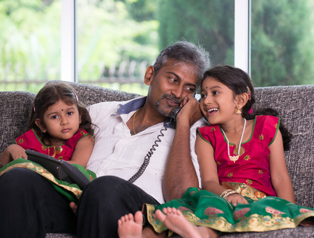 house call: indian father with his daughter on phone conversation lifestype photo