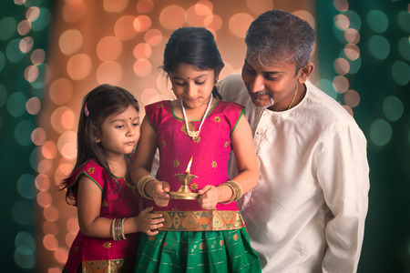 indian festival: indian family fagther and daughter celebrating diwali ,fesitval of lights inside a temple