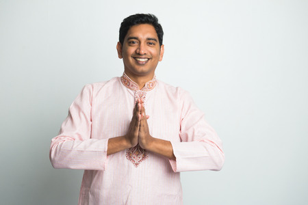 traditional young indian male with Pranamasana greetings sign on traditional dress with plain background