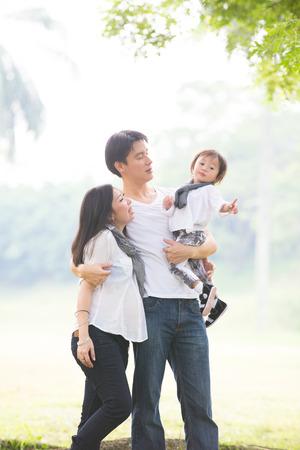 有丈夫和儿子室外照片的亚裔怀孕的母亲