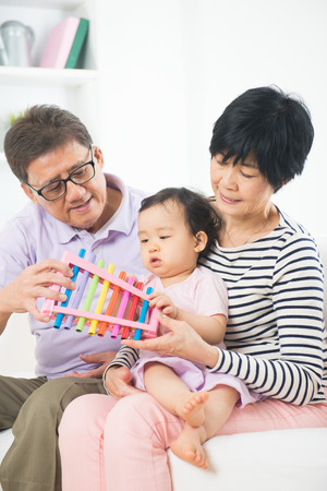 asian grand parents teaching granddaughter music lesson photo