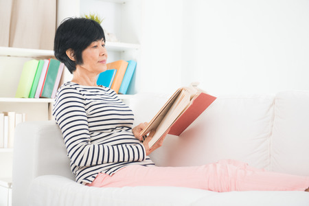 asian gereift ältere Frau liest auf einem Sofa